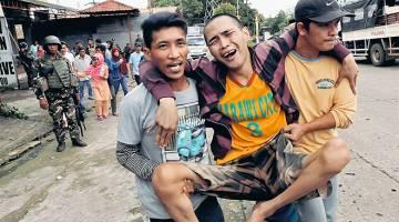NYAWA TERANCAM: Seorang penduduk dipapah ketika dipindahkan keluar dari bandar Marawi, semalam. — Gambar Reuters-
