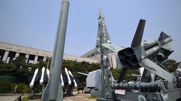 UJI LAGI: Seorang wanita melintasi replika misil Scud-B Korea Utara (kiri) dan misil Nike Korea Selatan (kanan) yang dipamerkan di Tugu Perang Korea di Seoul, semalam. — Gambar AFP