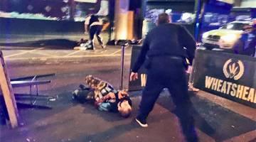 DAHSYAT: Dua daripada suspek terbaring selepas ditembak polis di tempat kejadian luar Borough Market, pasar tengah London, kelmarin. — Gambar Reuters/AFP