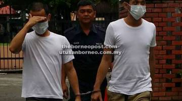 TENANG: Agus (kiri) diiringi anggota polis selepas prosiding.