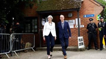 TUNAI KEWAJIPAN: May bersama suaminya Philip dilihat beredar dari pusat mengundi di Sonning, Britain semalam. — Gambar Reuters