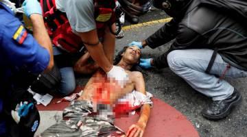 PARAH: Orang ramai cuba menyelamatkan nyawa seorang penunjuk perasaan yang cedera                  parah semasa protes terhadap kerajaan Maduro di Caracas, kelmarin. — Gambar Reuters