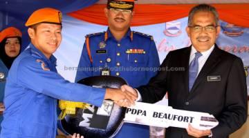 PERKUKUH OPERASI: Sukarti (kanan) menyerahkan Kenderaan Operasi dan Logistik Bencana Angkatan Pertahanan Awam Malaysia (APM) Fasa Pertama kepada wakil Pejabat Daerah Pertahanan Awam Beaufort semalam. Turut hadir Mulliadi (tengah). — Gambar Bernama