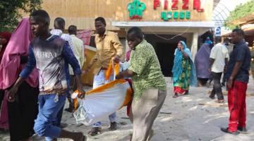 MAUT: Tiga lelaki mengangkat mayat mangsa terbunuh dalam serangan di sebuah restoran di Mogadishu, semalam. — Gambar Reuters