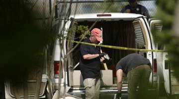 SIASAT: Ejen FBI dan penguat kuasa undang-undang lain memeriksa kenderaan dipercayai milik suspek selepas serangan tembakan semasa latihan perlawanan besbol amal untuk ahli Kongres Republikan di Eugene Simpson Statium Park di Alexandria, Virginia kelmarin. — Gambar AFP