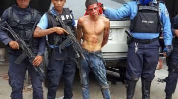 SUSPEK: Gambar serahan Polis Negara Honduras menunjukkan Alvaro Euceda (tengah) yang disyaki membunuh Funez, ketika dalam tahanan polis di La Ceiba, sebuah bandar 300 kilometer ke utara Tegucigalpa kelmarin. — Gambar AFP