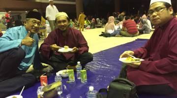 BERBUKA PUASA: Muhamad Yakup (kiri) berbuka puasa  bersama penduduk setempat di Dewan Suarah Bintulu.