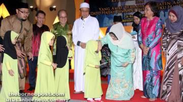 AMAL: Abang Johari menyaksikan Juma'ani menyampaikan sumbangan kepada anak-anak yatim pada Majlis Berbuka Puasa BN, malam kelmarin. Turut kelihatan Dr Sim (kiri), Uggah (dua kiri), Doreen (dua kanan) dan Rosey (kanan).