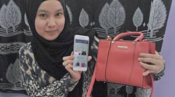KOLEKSI: Hidayah bersama salah satu koleksi beg tangan yang beliau beli dalam talian.
