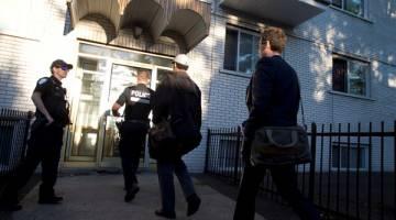 SIASAT: Penyiasat polis berjalan masuk ke kediaman Ftouhi di Montreal, Quebec, Kanada, kelmarin selepas Ftouhi dikenal pasti sebagai suspek oleh FBI dalam serangan pisau terhadap seorang anggota polis di lapangan terbang di Flint, Michigan. — Gambar Reuters