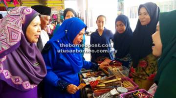 BAKAL USAHAWAN: Jainab (dua kiri) bersama Siti Salmiah (kiri) melawat tapak gerai jualan pelajar pada majlis itu.