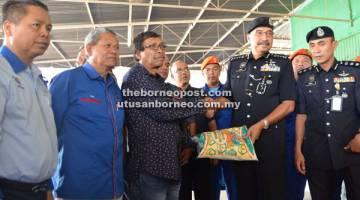 RINGANKAN BEBAN: Ramli menyerahkan sumbangan beras kepada wakil mangsa kebakaran di Kg Hidayat Laut, Batu 4 Jalan Apas.