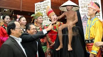 TINJAU: Rusmadi (dua kiri) bersama Wences (kiri) melihat maskot Tugu Siningazanak yang asalnya diambil daripada patung Siningazanak etnik Dusun dari Daerah Telipok yang merupakan simbol bagi keluarga yang tidak mempunyai anak sebagai pewaris harta terutamanya tanah pusaka di Kota Kinabalu, semalam. — Gambar Bernama
