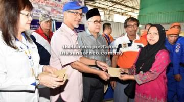 PRIHATIN: Tawfiq menyampaikan sumbangan kepada mangsa sambil diperhatikan oleh Mary dan Syed Abas.