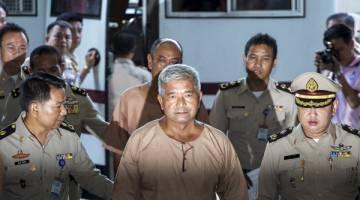 MEMALUKAN: Gambar fail 10 November, 2015 menunjukkan Manas dieskot para pegawai ketika tiba di Mahkamah Jenayah di Bangkok. — Gambar Reuters