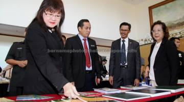 TERTARIK: Yap bersama Kamarudin (dua kiri) melihat buku hasil kajian yang dilakukan oleh UMS selepas melancarkan 'Inaugural BIMP-EAGA Higher Education Summit 2017'  semalam. — Gambar Bernama