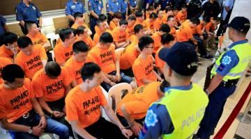 KES CULIK: Anggota polis berkawal di sekeliling suspek, majoriti warga China yang ditangkap kerana disyaki menculik seorang wanita Singapura di sebuah kasino, di Ibu Pejabat Polis Negara Filipina di Manila, semalam. — Gambar Reuters