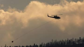 PADAM API: Helikopter turut menyertai usaha memadamkan kebakaran hutan di bandar Cache Creek, British Columbia di Kanada pada 18 Julai. — Gambar Reuters