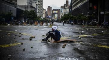TERUS LAWAN: Aktivis bertopeng duduk di atas jalan raya ketika memprotes terhadap Maduro di Caracas, kelmarin. — Gambar AFP