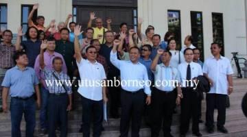 Henry (tengah) bersama komuniti Bisingai di luar Mahkamah Kuching selepas sebulat suara menarik balik tuntutan mahkamah terhadap kerajaan negeri berhubung isu tanah Pimu'ung.