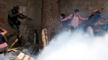 KEJAR: Anggota polis bersenjata mengejar penunjuk perasaan anti-Maduro di Caracas, Venezuela kelmarin. — Gambar Reuters