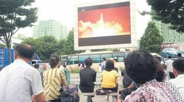 BANGGA: Penduduk Korea Utara menyaksikan pelancaran ujian misil ICBM yang dipaparkan pada skrin gergasi di dataran awam di Pyongyang, semalam. — Gambar AFP