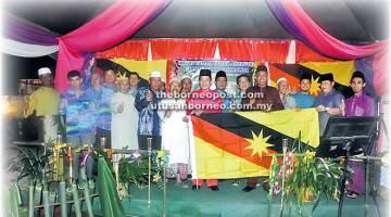 SEMANGAT PATRIOTIK: Hussaini (sepuluh kiri) Mohd Amran (lima kanan), Awang Emran (dua kanan) bersama ahli-ahli KRT Batong mengibar bendera Sarawak.