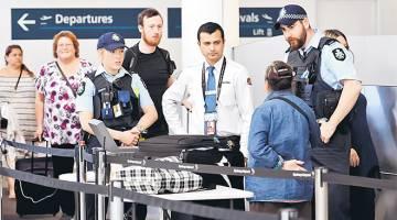 DIPERKETAT: Anggota polis persekutuan membantu menapis penumpang di Lapangan Terbang Antarabangsa Sydney di Sydney, semalam. — Gambar AFP