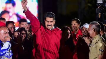 MABUK KUASA: Maduro (tengah) dan para penyokongnya bersorak-sorai meraikan keputusan Dewan Perlembagaan di Caracas, semalam. — Gambar AFP