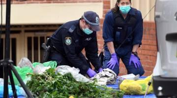 DITELITI: Anggota polis menyelongkar sampah-sarap untuk mencari bahan bukti di blok pangsapuri di Lakemba, pinggir Sydney semalam selepas serbuan antiterorisme di seluruh bandar tersebut kelmarin. — Gambar AFP