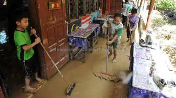 BANJIR KILAT: Murid-murid SRK Darau Menggatal membersihkan sekolah mereka yang teruk dilanda banjir berikutan hujan semalam. — Gambar Bernama