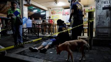 SIASAT: Pegawai polis memeriksa mayat seorang lelaki yang menurut mereka ditembak mati dalam pembunuhan berkaitan dadah di Manila, Filipina kelmarin. — Gambar Reuters