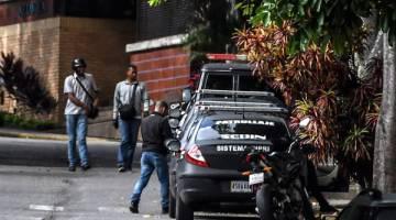 SERBU: Pegawai badan perisikan SEBIN dilihat berkawal di luar rumah Ortega di Caracas, Venezuela kelmarin. — Gambar AFP