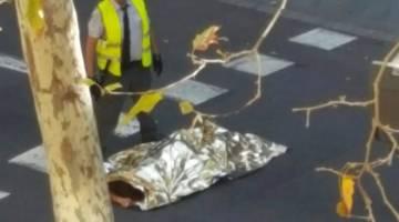 MALANG: Mayat mangsa ditutupi kain terbaring di atas jalan raya selepas sebuah van merempuh pejalan kaki berhampiran lebuh Las Ramblas di tengah Barcelona, Sepanyol kelmarin. — Gambar Reuters