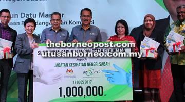 PROMOSI: Nasrun (tengah) bersama Christina (tiga kanan) dan Ahmad Lai (tiga kiri) bersama pegawai kanan JKNS yang lain semasa majlis penyampaian 1 juta sarung tangan perubatan kepada JKNS.