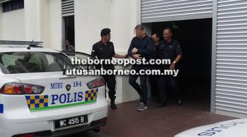 TANGGUH: Fitri dieskot keluar dari bangunan mahkamah menuju ke kenderaan polis.