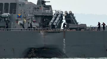 KEMALANGAN LAGI: Kesan pelanggaran dapat dilihat pada bahagian tepi kapal pemusnah berpeluru berpandu USS John S. McCain di luar pangkalan tentera laut Changi di Singapura, semalam. — Gambar AFP
