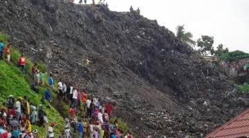 TERTIMBUS: Orang ramai mengerumuni tempat kejadian di tapak pelupusan sampah di kawasan kejiranan Dar Es Salam di pinggir Conakry, kelmarin. — Gambar Reuters