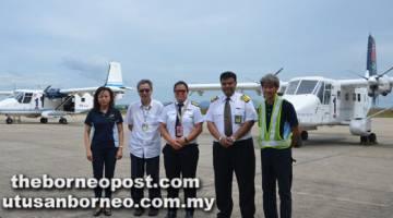 KERJA MENCABAR: (Dua dari kanan) Irwin, Kam dan Chan bersama kakitangan LLA yang lain semasa meninjau pesawat yang dikendalikan syarikat itu.