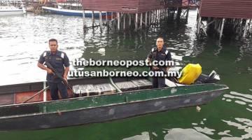 DIRAMPAS: Dua anggota APMM mengiringi bot yang membawa 15 kotak rokok ke Jeti Semporna.