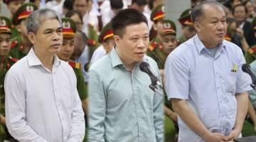 DIDAKWA: Kombinasi gambar menunjukkan (dari kiri) Nguyen Xuan Son, Ha Van Tham dan Pham Chong Danh dalam perbicaraan di Mahkamah Rakyat di Hanoi, semalam. — Gambar AFP