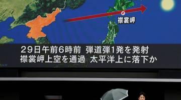MENGEJUTKAN: Skrin TV gergasi menunjukkan berita mengenai pelancaran misil Korea Utara di Tokyo, semalam. — Gambar Reuters
