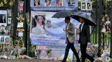 TERUS DIKENANG: William dan Harry melihat tanda penghormatan oleh orang ramai untuk ibu mereka di hadapan Istana Kensington di London kelmarin. — Gambar AFP