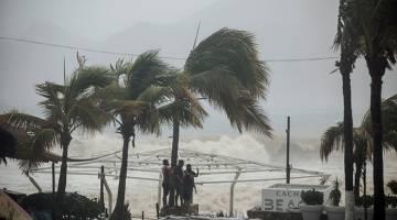 BERGELORA: Pelancong melihat ombak bergelora ketika Taufan Tropika Lidia membadai Los Cabos di Mexico kelmarin. — Gambar Reuters