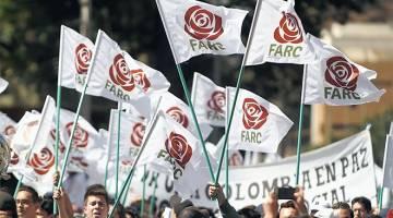SOKONGAN PADU: Ahli dan penyokong FARC berarak sambil membawa bendera tertera logo baharu FARC yang kini menjadi sebuah parti politik semasa penutupan Kongres Kebangsaan di Bogota. — Gambar AFP