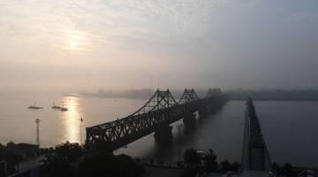 PERANG NUKLEAR: Bandar Korea Utara Sinuiju melatari pemandangan di seberang Jambatan Persahabatan (kiri) yang menghubungkannya dengan bandar sempadan China Dandong, dan Jambatan Patah di Dandong dalam wilayah timur laut Liaoning semalam. — Gambar AFP
