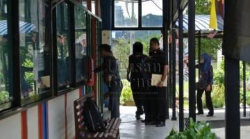 TUNTUTAN PALSU: Tertuduh (tengah) memasuki Mahkamah Majistret Limbang, ditemani pegawai SPRM Limbang pagi tadi
