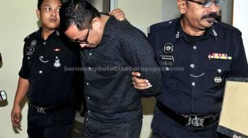TERTUDUH: Badril Hisham Abu Mansor, 40, (tengah) dihadapkan ke Mahkamah Majistret semalam, atas pertuduhan membunuh seorang eksekutif pemasaran Tan Chai Soon, 46, di sebuah hotel di Stulang Laut pada 3 Sept lepas. — Gambar Bernama