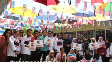 WARNA-WARNI MALAYSIA: Abal Mukam (lima kiri) dan Ag Roslan (enam kiri) bersama Pengerusi Permuafakatan Komuniti 1Malaysia Negeri Sabah Tahir Mohd Soon (tujuh kiri) semasa Majlis Pelancaran Anjung Payung Merdeka SMK Putatan.