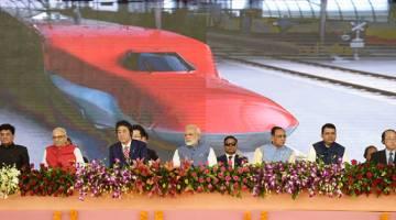 KERJASAMA: Gambar serahan Biro Maklumat Media India menunjukkan Modi (tengah) dan Abe (tiga kiri) pada majlis melancarkan projek kereta api peluru di Ahmedabad semalam. — Gambar AFP